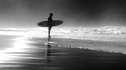 The surfer between the fog and the sea.
